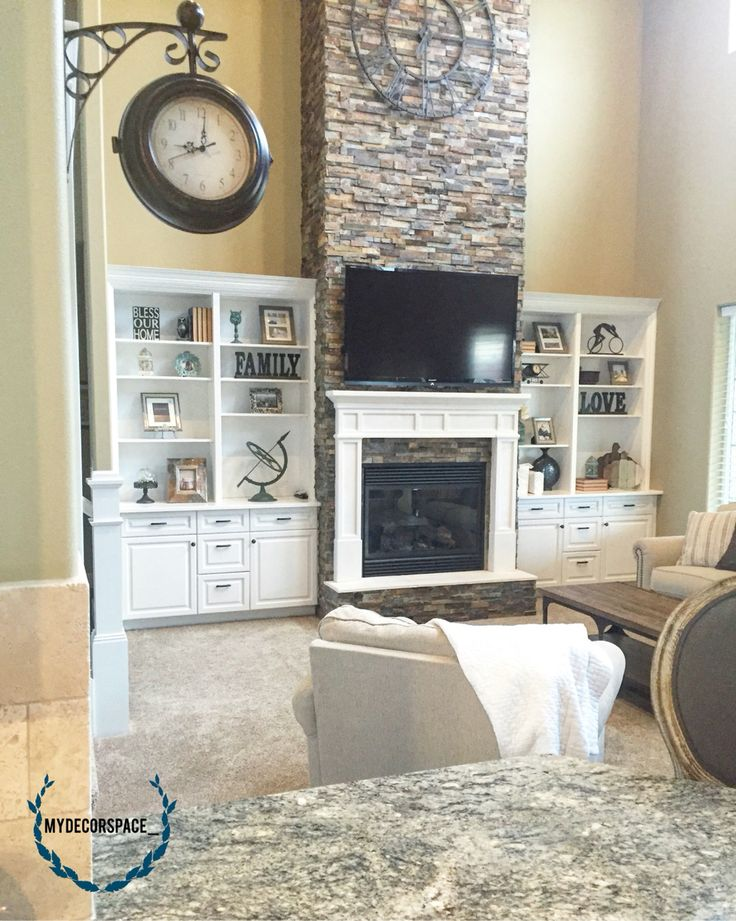 Great room living room family room fireplace rock mantle fireplace mantle built in shelves builtins book cases bookcase decor large clock oversized lock two story family room two story great room vaulted ceiling open concept living open concept