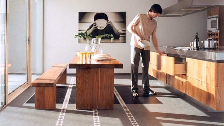 Private living area: man in kitchen takes plates from a drawer. Grey kitchen floor of Forbo linoleum.