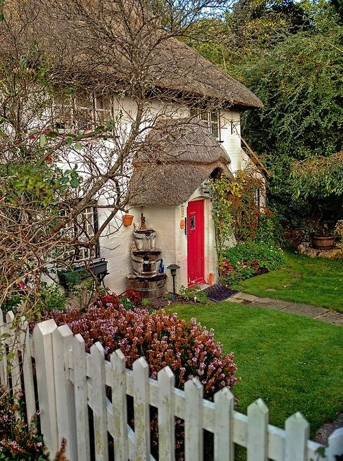Thatch roof, red door, picket fence
