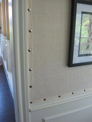 She covered her breakfast room walls with burlap. She trimmed the edges and finished them with what looks like upholstery tacks, giving the rough-and-tumble material a very polished and tailored appearance: