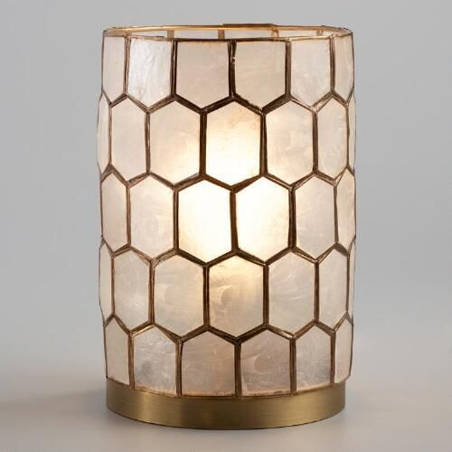 Artisans in the Philippines harvest natural capiz shells and cut them expertly by hand to create our honeycomb lamp. Turn it on to illuminate each translucent seashell in the gold-finished frame and fill your desk or tabletop with a warm, ambient glow.
