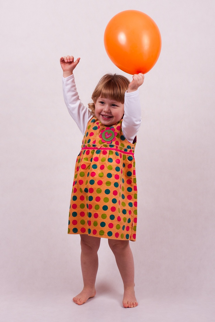 Dress without sleeves. Pattern with big, color dots and with flower motif on the front. Zip fastening at back. Material is safe in contact with sensitive skin of your baby.