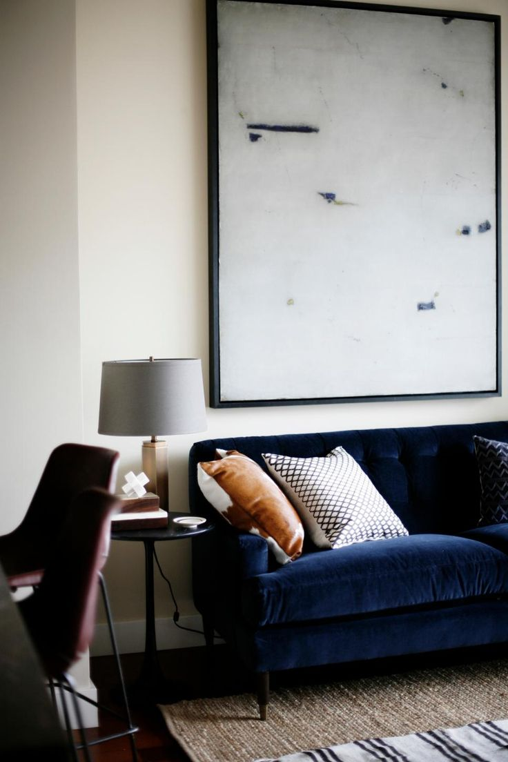 touches of navy and sangria with black and, flax and and white - This bright living space with contemporary and midcentury modern influence features a navy blue velvet sofa, a mix of throw pillows and minimalist artwork framed above the sofa.