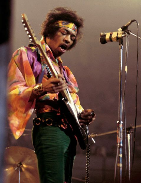 Jimi Hendrix performing in London, Feb. 24, 1969.  Died Sept. 18, 1970, age 27.  In four years, he went from obscurity to being a legend, so pictures of him are from the hippie era:  fringed jackets, velvet suits, ruffled shirts, bell bottoms, bright colours, etc.  More info at https://en.m.wikipedia.org/wiki/Jimi_Hendrix.