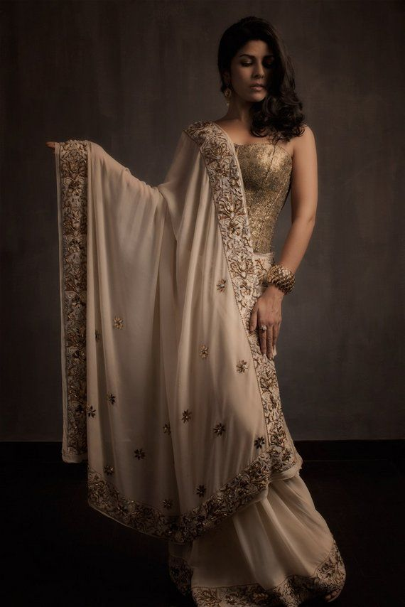 Gown: Cream coloured georgette sari with extensive zardosi, stone and moti work on the border, along with exquisite floral sequin work on the pallu.
