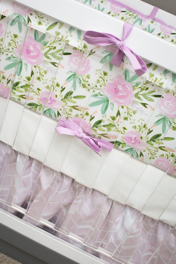 This completely custom baby bedding gives a wildflower boho vibe with watercolor floral bumpers and a feather herringbone crib skirt in soft lilac and