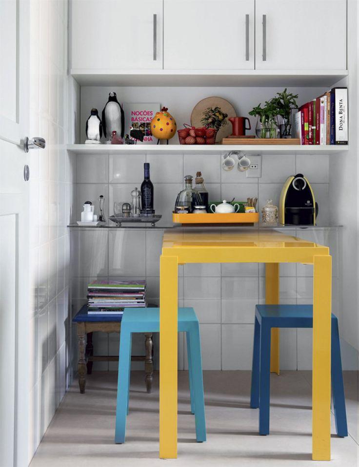 Encaixada sob a prateleira de acrílico, a mesa é usada no café da manhã. O armário do alto acomoda xícaras, jarras e utensílios de fondue. Bancos da Tidelli.