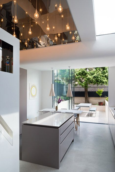 Reflective stainless steel surfaces and a polished concrete floor brighten the interior of this extension to a terraced house in London
