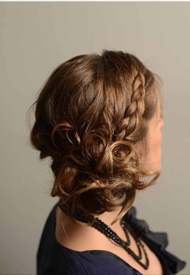 Side swept low bun/curls with side sweeping braid and bangs.