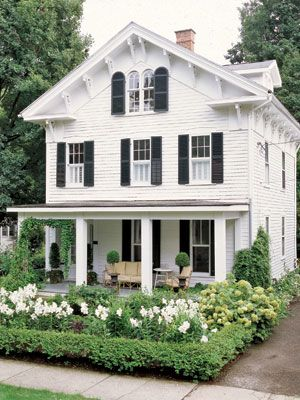 White house, black shutters, large front porch, beautiful flowers = great curb
