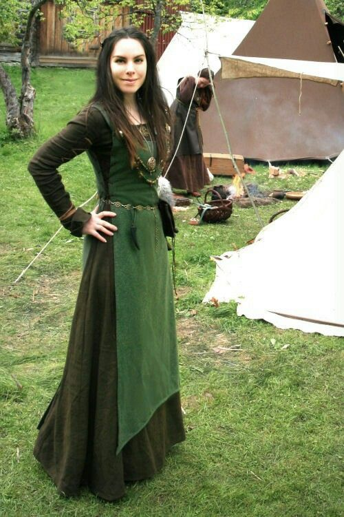 I like the length and uneven hem of her overdress. I also like the tonal look with the green-on-green layering.