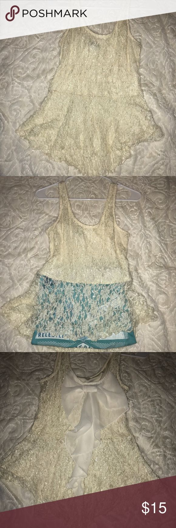 Shimmy cream gold tank Shimmy cream gold tank from rue 21 with bow detail on back. Is see through below ribs (not acutely blue underneath just put a shirt there for contrast 😂)  **TAG SAYS LARGE BUT DEFINITELY FITS MORE SNUG LIKE A MEDIUM** Rue 21 Tops