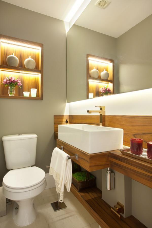 Banheiro com bancada e nicho embutido em madeira. Espelho e nicho com iluminação embutidas. Parede em cinza concreto e metais em cobre. Decoração contemporânea e aconchegante. Projeto de reforma e design de interiores para apartamento de 170 m2 na Pompeia, São Paulo.