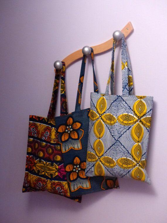 Ce tote bag avec ses lignes bleue et jaune est idéal pour les petites courses ou pour transporter ses affaires très simplement. Avec son tissu au motif géométrique, il sera parfait pour égayer n'importe quel jour de l'année.  Sac en wax 36cm x 40cm Anses longues (environ 60cm)