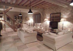 Magnifique ! Ce salon est créé sur le principe campagne chic avec au sol des pierres de bourgogne de différents coloris. Un mur de pierre juste superbe quand au mobilier, il a un coloris neutre qui va parfaitement avec l'ensemble . La cuisine est réaliser de la même manière avec un mobilier noir qui donne un côté chic à l'ensemble