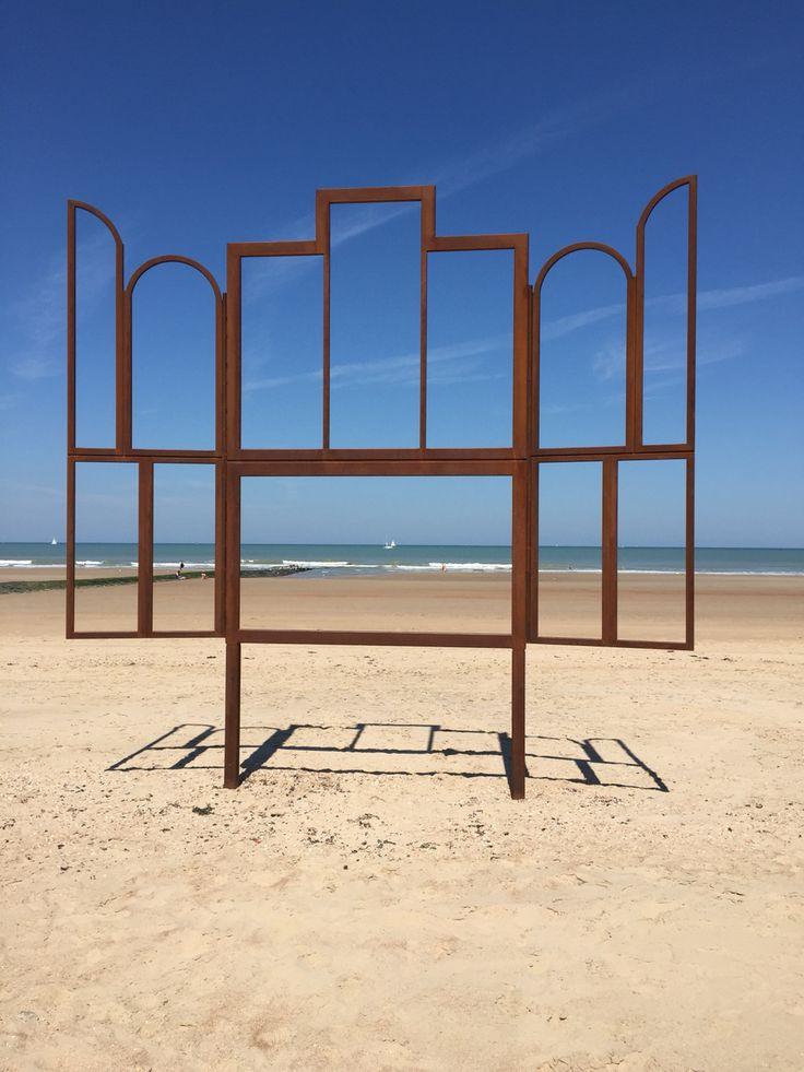 """Jan Hoet Oostende Mu.ZEE 't Lam Gods De zee - salut d'honneur 'Altar' is het enige werk van de tentoonstelling dat op het strand staat. Dat was ook de keuze van de kunstenaar. We zien een leeg altaar, de panelen zijn weg, de structuur blijft over. """"Jan zei altijd: """"Kijk, kijk naar de lucht, je moet kijken!"""""""" gaat Kris Martin verder. """"Dit is een open venster, een venster op de zee in dit geval. De kadrage verandert naarmate je dichtbij of veraf staat. Het creëert een soort van tableau…"""