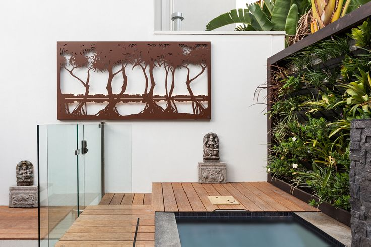 Laser cut 'Pandanus Wetland' by the pool in Port Melbourne. With LED strip lighting as a sunset. Installation by Kihara landscapes.