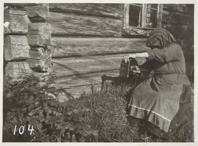 """Maaninkalainen vanhus kutoo """"mytkä-"""" eli pirtanauhaa aurinkoisella ulkoseinustalla Rytkönen Ahti. 1928"""