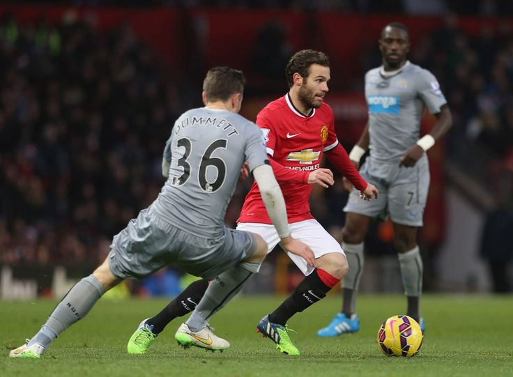 Juan Mata of Manchester United in action with Paul Dummett of Newcastle United