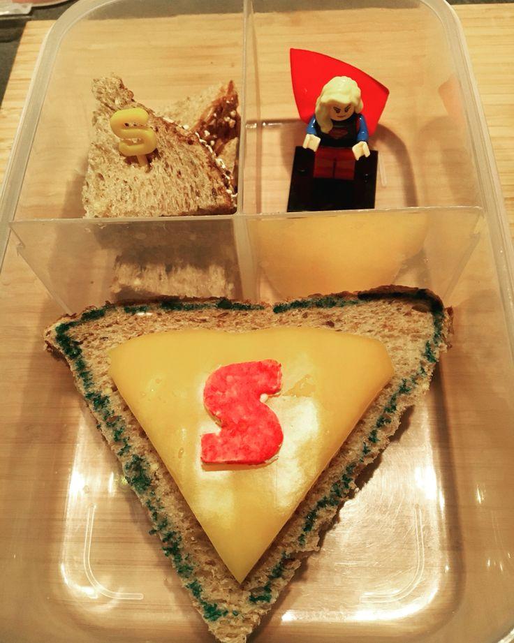 Superwomanlunch  1) Volkorenboterham met worst, in een driehoek gesneden.  2) Van gele paprika ook een driehoek gesneden en erop gelegd en vastgeplakt met n beetje creamcheese.  3) Uit een wrap met een uitsteker een S gestoken, en deze rood gekleurd met stift met eetbare inkt. En met creamcheese erop geplakt. 4) De restjes brood heb ik besmeerd met appelstroop en er een letterprikker ingestoken. De worst die erop zat, hebben de meiden alvast opgesnoept. 5) LEGO superwoman popje erbij en…