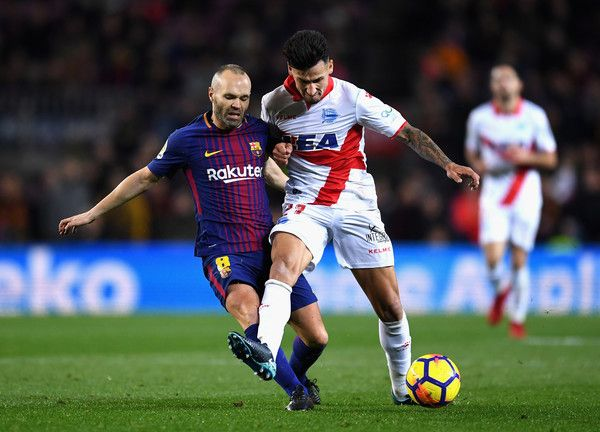 Andres Iniesta of Barcelona is tackled by Hernan Perez of Alaves during the La Liga match between Barcelona and Deportivo Alaves at Camp Nou on January 28, 2018 in Barcelona, .