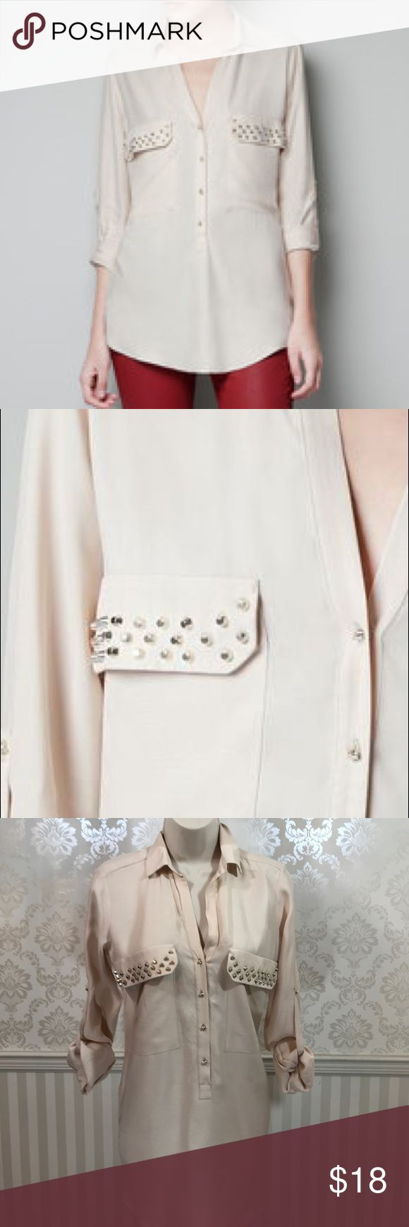 """Zara Blouse with Studded Pockets Zara cream-colored blouse in perfect condition. Silver studs on front pockets. Would look great with a leather jacket and jeans! Silver skull buttons. Button tab sleeves. Split hemline. Slouchy fit. Bust is about 38,"""" length is approximately 31"""" at longest point. 100% viscose. Size XS. Zara Tops Button Down Shirts"""