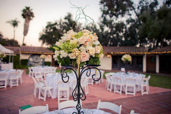 Beautiful centerpiece at outdoor wedding - arrangement of light pink, peach, light green, ivory, and white flowers attached to a black wrought iron candelabra