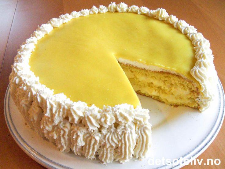 """""""Romkremkake"""" består av en lett og luftig sukkerbrødsbunn som fylles med deilig romkrem. Kaken pyntes med pisket krem og et dekorativt lokk av gul marsipan. En nydelig bløtkake!"""