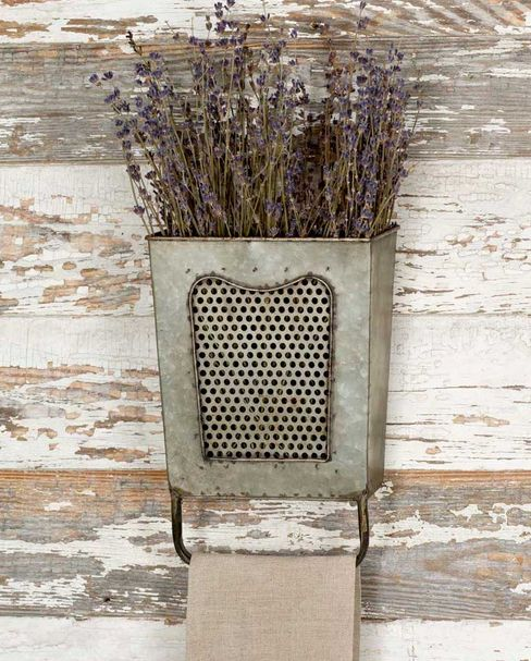 A rustic towel bar for bath or kitchen.  Metal pocket can hold dried flowers, more towels or anything you desire to create a great piece of wall decor.