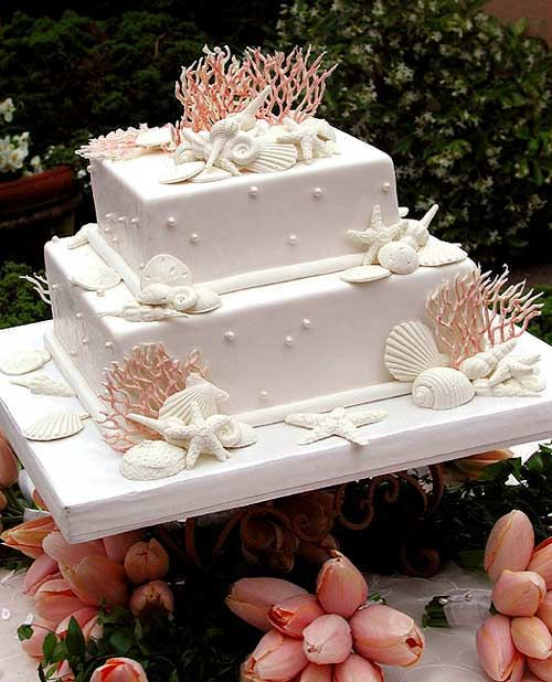 Stunning two tier white beach, seashell wedding cake decorated with edible white pearls, orange sea coral, white edible seashells and surrounded by apricot coloured tulip bouquets. Perfect for a summer theme wedding. From www.justfab.com                         #wedding #cake #birthday
