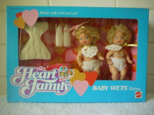 The Heart Family Baby Wets Babies - 1987 - RARE by Mattel. $69.99. This set includes a blonde baby boy doll with curly hair and a blonde baby girl doll with bangs and long blonde hair, 2 cloth diapers, 2 bibs, 4 disposable diapers, 2 bottles, a pink brush, a label sheet and instructions.  The babies really drink from their bottles and wet their diapers.