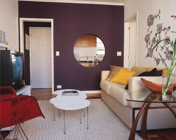 gostei da parede roxa com a abertura redonda para a cozinha, e da mesinha de vidro ao lado do sofá.