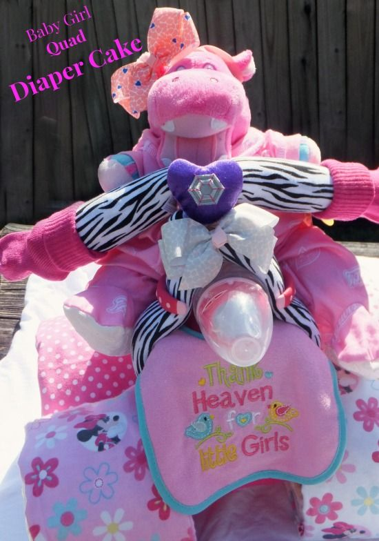 """Baby Girl """"Quad"""" Diaper Cake This adorable Baby Girl Quad 4x4 Diaper Cake is made of 50 (size 1) Pamper Diapers, 1 Plastic Tub of Wipes,  1 Sleeper, 4 Receiving Blankets, 2 Bibs, 2 Snuggle Wraps, 1 Sippy Cup, 2 Hair Bows, 2 Wrist Rattles, 1 pair socks and 1 Matching Stuffed Animal. These can be customized to a Theme (This one was New England Patriots,)"""