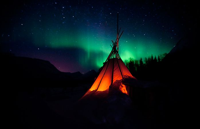 A typical Norwegian lavvo tent under the Aurora.