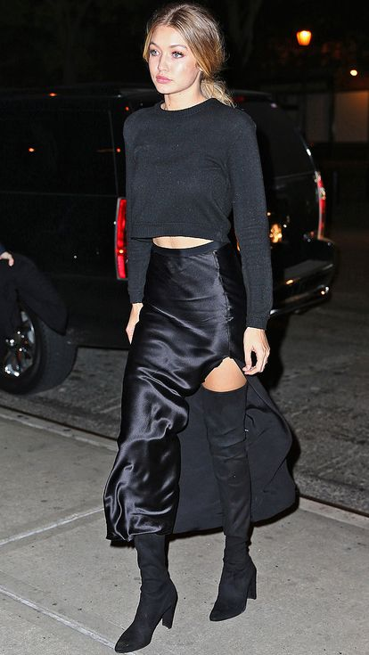 """If there was such a thing as """"casual-glam,"""" it would look like Gigi Hadid's all-black ensemble here, which mixes low-key silhouettes with high-end fabrics (her cashmere Everlane sweater, satin slit skirt and thigh-high stretch leather Stuart Weitzman boots)."""