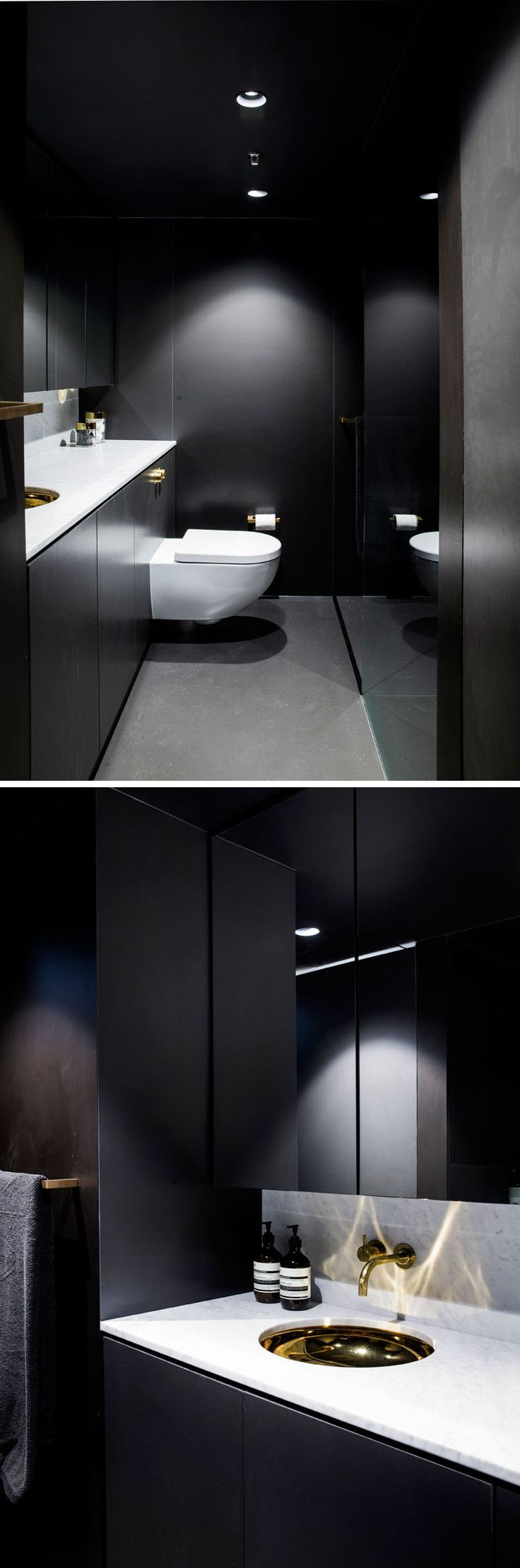 This dramatic black bathroom features a floor-to-ceiling mirror, grey flooring, a white countertop and gold accents.