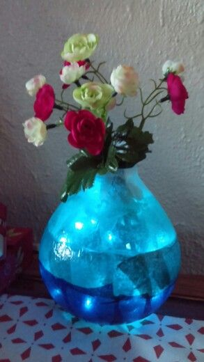 White and different blue tissue paper on the vase. There are blue Christmas lights inside the vase.  A stem of flowers are just placed inside.  When the lights are plugged in, it looks like real water inside the vase.  I made this with different flowers even put berry stem for a Japanese look.