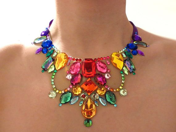 This sparkling jeweled statement necklace is created using bright, colorful rhinestones in a rainbow gradient pattern. When worn, the sheer fabric backing creates a dramatic and beautiful eye-catching illusion! Beautiful colorful acrylic rhinestones sparkle at every angle and make for a truly ...