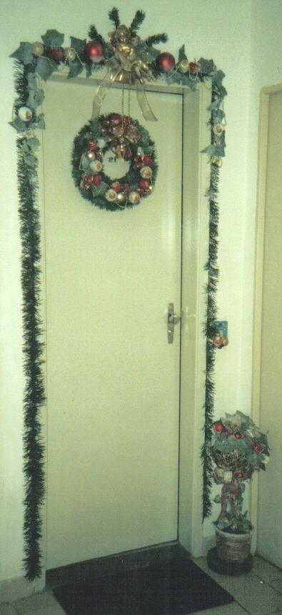 Porta de apartamento tora decorada, com guirlanda, topiaria de chão, espelho de campainha e enfeite adornando todo o batente da porta, com tema natalino nos tons verde fosco, vermelho, e detalhes ouro e branco. Elo7 - Mimos da Zelia.