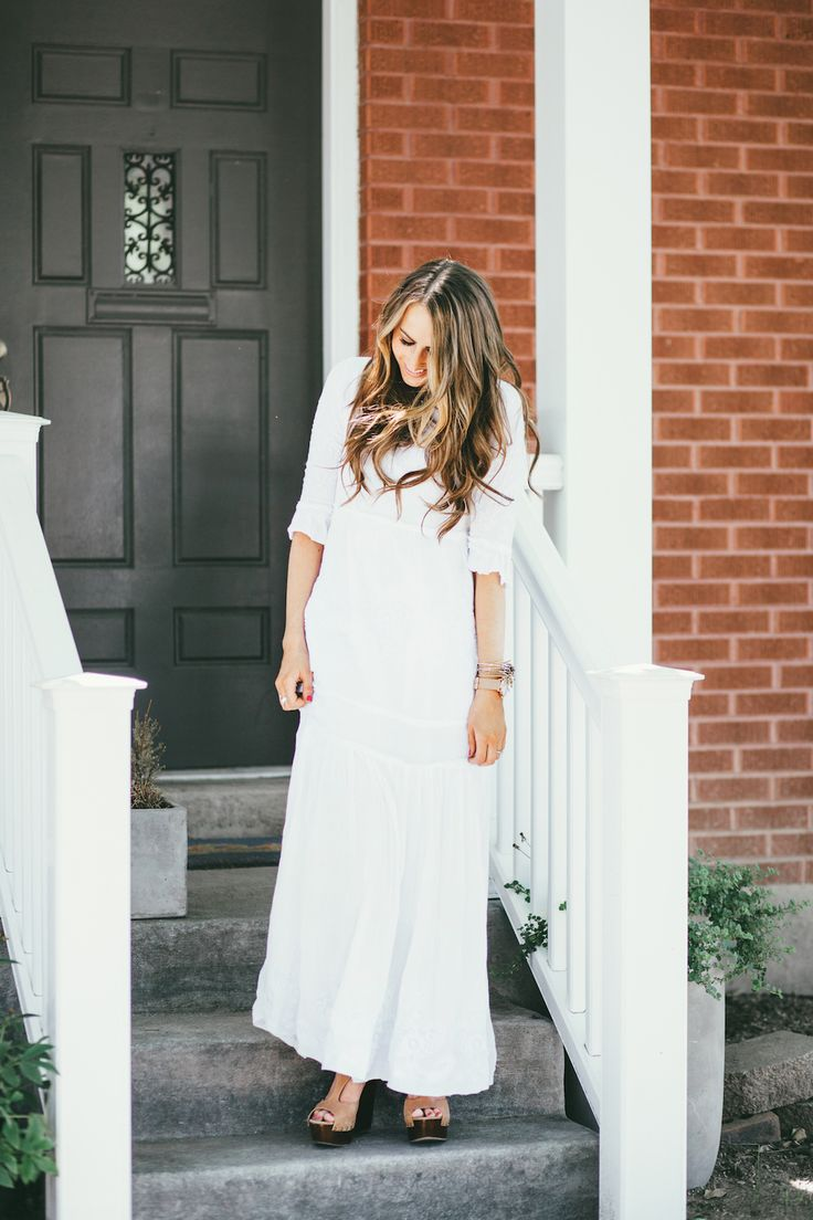 Girl in long white embroidered maxi dress with long loose caramel and brown curls. The simplicity of this maxi dress is beautiful!