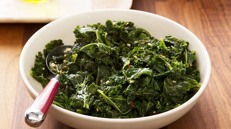 bowl of cooked kale resting on a wooden table with a spoon dug halfway into the food