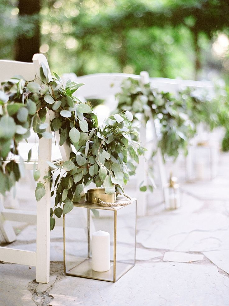 outdoor wedding ceremony decor   simple white folding chairs on the aisle draped with greenery garland and gold lanterns with pillar candles   Dreaming of a Fairytale Wedding in the Redwoods? Look No Further!