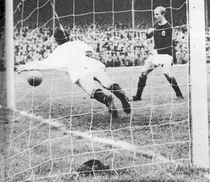 2nd October 1965. Northern Ireland centre forward Willie Irvine (not in picture) scores past Scotland goalkeeper Bill Brown while winger Jimmy Johnstone watches on during the Home International, at Windsor Park.