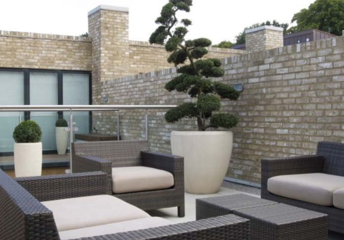 contemporary roof terrace - chic all weather rattan lounge furniture and box balls/cloud topiary in lightweight limestone effect modern planters | Paul Dracott Garden Design Cambridgeshire Uk | Roof Terraces - Does anyone know where I can purchase similar planters in the UK please?