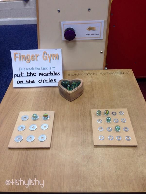 Glue washers to board. Container with marbles.  Place marbles inside washers.