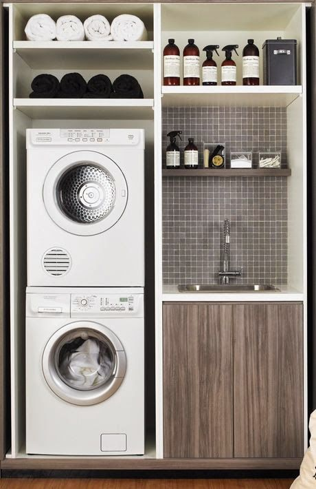 Small laundry room ideas: diy shelves and sink in tiny laundry area with stackable washer and dryer.