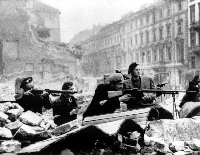 Polish partisans in position behind a barricade on Mazowiecka Street