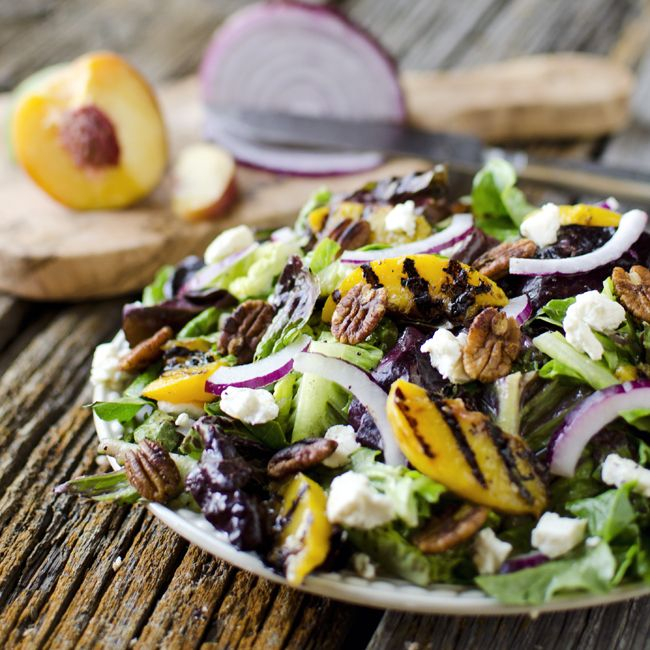 A bed of mixed greens tossed with a citrus poppy seed dressing, grilled peaches, honey goat cheese, spiced pecans and red onions for a spectacular salad!