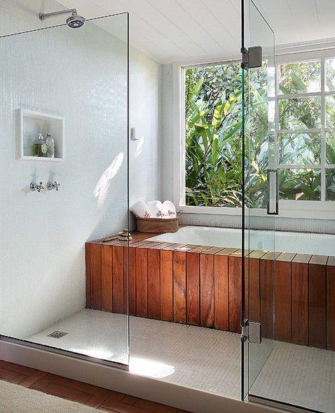 O box fechado por vidros abriga a área do chuveiro, revestida por pastilhas brancas, e banheira envolvida por madeira de deque. A grande jan...