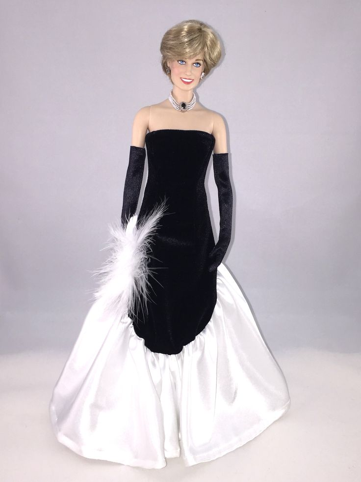 This Franklin Mint Diana doll is wearing a custom replica of a gown with a black velvet bodice with white taffeta skirt designed by Murray Arbeid. This gown was worn by Diana to attend The Worshipful Company of Fan Makers Banquet at Mansion House in December 1985. The gown also came with a black velvet bolero but most pictures show Diana wearing the gown without the bolero. Christies Lot 49.